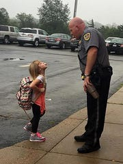 Mackenna Jensen (left) and Cotter School Resource Officer Jeremy Melton share a light-hearted moment on the opening day of school Monday in Cotter.