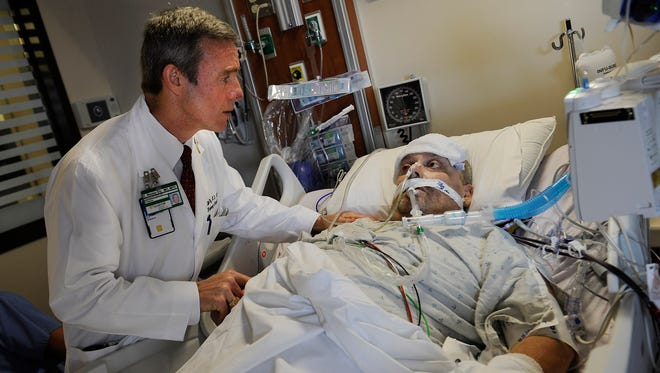 Dr. Wes Ely evaluates ICU patient Carl Pangman at Vanderbilt University Medical Center on Tuesday, Oct. 1, 2013, in Nashville, Tenn. Ely was one of the authors of the study looking at long-term cognitive impairment after a critical illness.