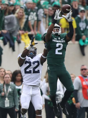 Michigan State Spartans CB Darian Hicks intercepts a pass in front of Michigan Wolverines RB Karan Higdon during the third quarter Saturday, Oct. 29, 2016 at Spartan Stadium in East Lansing.