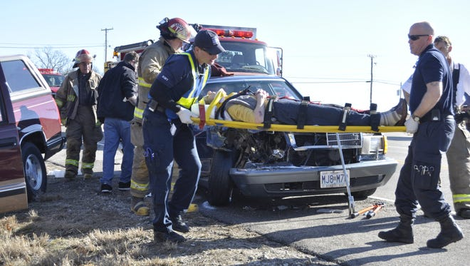 Emergency personnel carry Garnet Trosper, 88, to a waiting ambulance at the scene of a two-vehicle accident on U.S. Highway 62 at Denton Ferry Road in Cotter on Saturday morning.