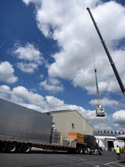 A crane lifts a huge smokehouse to the top of the Godshall's