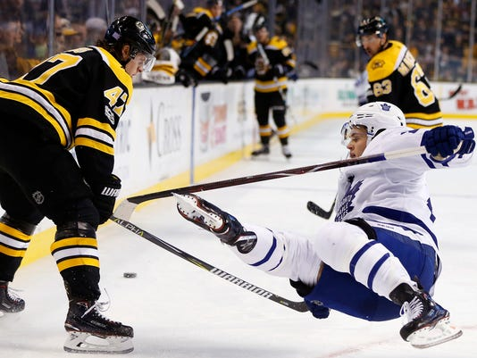 Toronto Maple Leafs' William Nylander, right, falls after being checked by Boston Bruins' Torey Krug (47) during the first period of an NHL hockey game in Boston, Saturday, Nov. 11, 2017. ((AP Photo/Michael Dwyer)