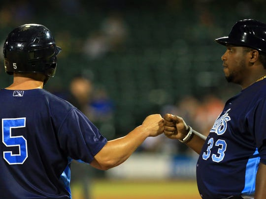 Hooks' Jack Mayfield fist bumps manager Rodney Linares after arriving to third base against Frisco on Saturday, June 24, 2017, at Whataburger Field in Corpus Christi.