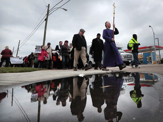 Dean Andy Andrews of St. Mary's Episcopal carries the same cross Sunday afternoon that was used in the 1968 march as he leads a procession of parishioners and religious leaders along Poplar Ave. in honor of the April 5, 1968 march by local clergy that sought to end the sanitation strike.