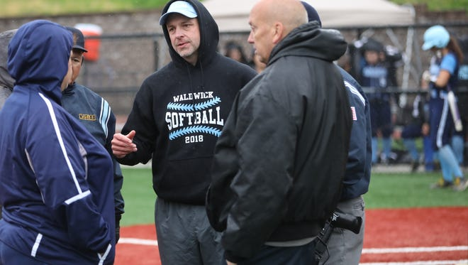 Waldwick coach Mike Kilgallen and Immaculate Conception coach Jeff Horohonich meet with umpires to discuss halting their game Sunday at Holy Angels. The game will be picked up in the top of the 2nd inning with no score.