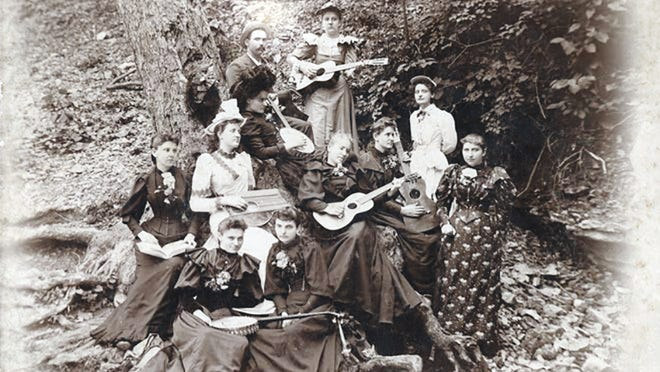 Portrait of a band seated around a tree holding guitars and banjos. The man in the back is Zeran Lawson and the woman with the white guitar is Hattie Hart Thompson. Both were from Newton County, Missouri. STATE HISTORICAL SOCIETY OF MISSOURI