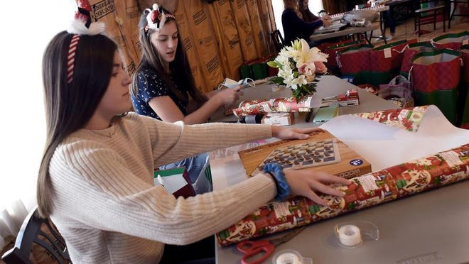 Jefferson High School students and members of the  Honor Society include sophomore Emmi Liptow, juniors Kirsten Vanisacker, Laynie Tipton, Marissa Manley, and Lily Liptow wrap hundreds of gifts for the residents of local nursing home as part of `Ray 4 Hope' at Bacarella Funeral Home in Monroe Saturday.