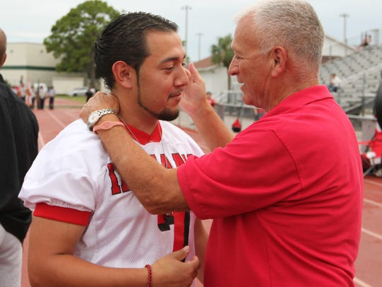 Former Immokalee football coach John Weber congratulates Phillip Perez, of the 2004 state championship team, after team members and coaches were honored prior to a game against Barron Collier on Friday night.