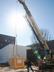 A rocket payload, packed in a wooden box, is being taken out of the ground Feb. 11 near Van Allen Hall on a crane. The payload, devloped by a UI team, will be launched into space from New Mexico later this year.