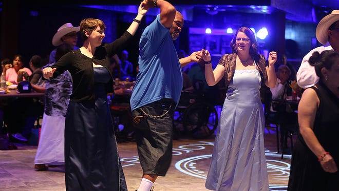 Prom goers Andrew Coleman dances with Teresa Jaston (left) and Samantha Jaston during MHMR's A Night to Shine prom at the KORONAZZ Nightclub Friday, June 1, 2018.