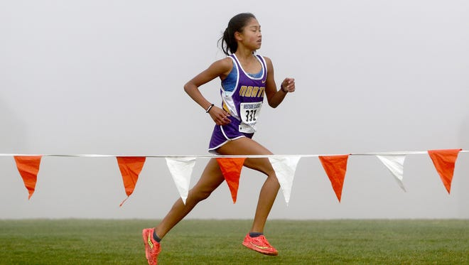 North Kitsap's Madison Zosa runs through the fog during Saturday's district cross country meet at Chambers Bay in University Place.