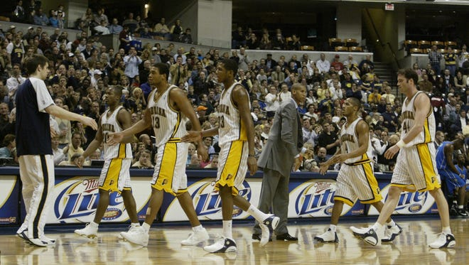 Indiana Pacers guard Reggie Miller, third from right, greets the Pacers starters, from left, Fred Jones, David Harrison, James Jones, Eddie Gill and Austin Croshere, as they walk towards the bench during a timeout against the Orlando Magic in the first quarter iin Indianapolis.