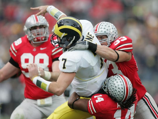 Michigan's Chad Henne is forced to throw the ball away