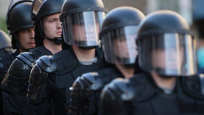 Riot police stand in formation in 2015 as a protest forms against the acquittal of Michael Brelo, a patrolman charged in the shooting deaths of two unarmed suspects in Cleveland. The city of Cleveland reached a settlement with the U.S. Justice Department over a pattern of excessive force and civil rights violations by its police department.