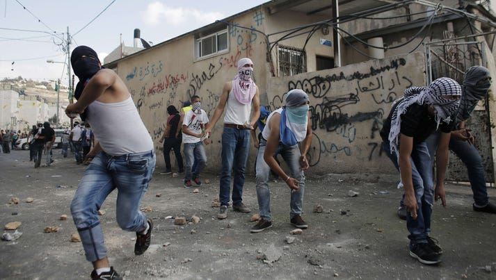 Palestinian youths hurl stones at Israeli policemen during a protest of the death of Mohammed Sinokrot in east Jerusalem on Sept. 7, 2014.