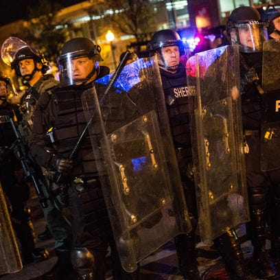 Riot police enforce a 10 p.m. curfew and clear the