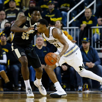 Michigan guard Zak Irvin (21) moves the ball defended