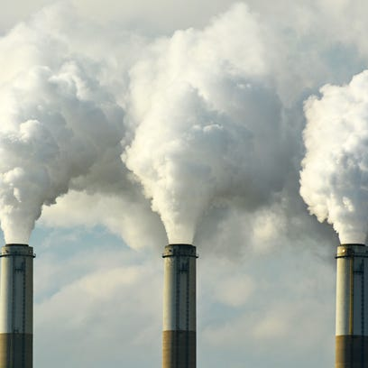 Multiple coal fossil fuel power plant smokestacks emit