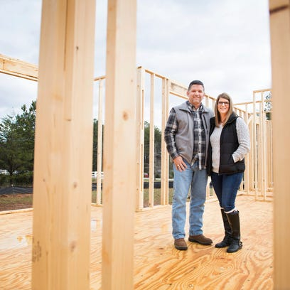 Chad and Melissa Albertson stand in one of the homes