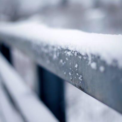 Snow covers a rail of a bridge on Prospect Avenue Monday,