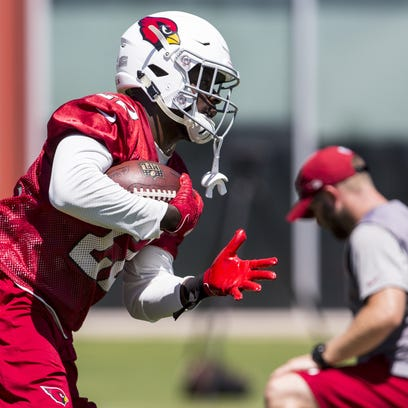 Cardinals running back T.J. Logan performs a drill