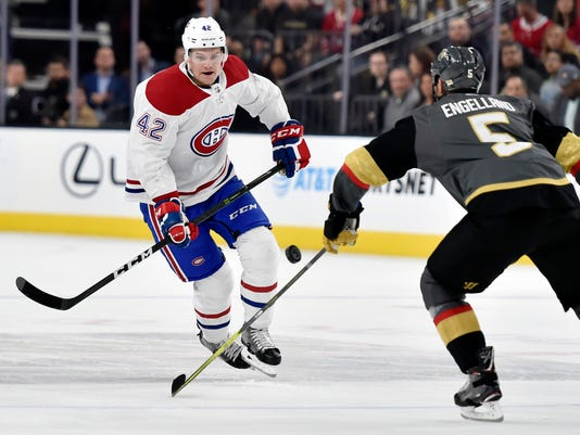 Montreal Canadiens center Byron Froese (42) and Vegas Golden Knights defenseman Deryk Engelland go after the puck during the first period of an NHL hockey game Saturday, Feb. 17, 2018, in Las Vegas. (AP Photo/David Becker)