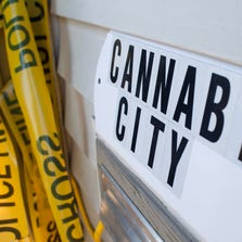 A sign is pictured near police tape, which was used as a prop for a ribbon cutting ceremony, at Cannabis City, a retail marijuana store, on July 8, 2014 in Seattle, Washington. Cannabis City was the first retail marijuana store to open in Seattle on July 8 and one of many now operating in Washington state, nearly a year and a half after the state's voters chose to legalize marijuana.