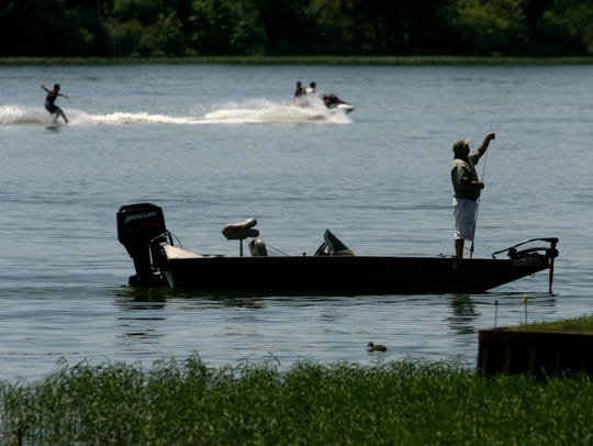 As water skiers enjoy a beautiful summer day on Geist Reservoir on July 16, 2007, fisherman Mark Swafford, Fortville, prepares to cast for largemouth bass along the banks of the reservoir along Fall Creek Road.