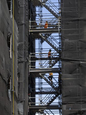 Workers scale a scaffolding between wings of the 5th Street Public Market expansion in downtown Eugene. [Chris Pietsch/The Register-Guard] - registerguard.com