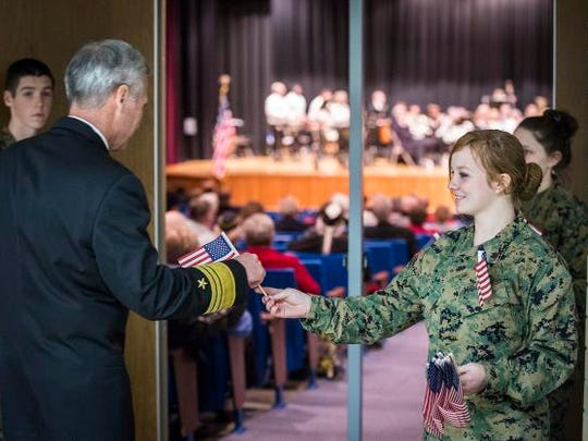 A Central JROTC member hands Vice Admiral James Syring a flag as he enters the auditorium before his keynote speech on Veteran's Day.