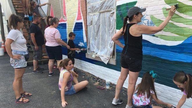 Muralist Leah Tumerman looks on as volunteers help apply sealer to her work on Second Street Sunday.