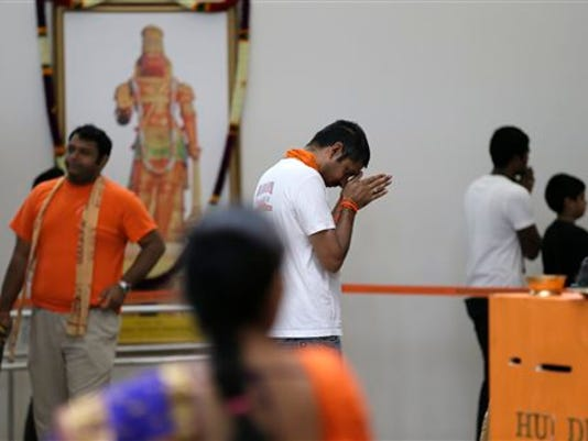 In this photo made Saturday, Aug. 22, 2015, a devotee prays at the Karya Siddhi Hanuman Temple that serves the Asian Indian community in Frisco, Texas.