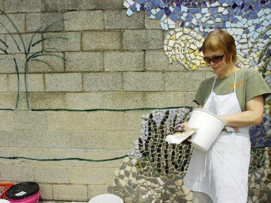 Mary Cantrell Tellez looks through a bucket for just the right ceramic piece while working on the mosaic in May 2010.