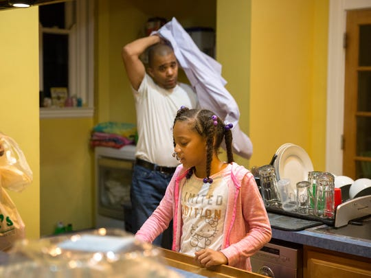 Camille makes her lunch for school as her dad, Christopher gets ready for a workday​.