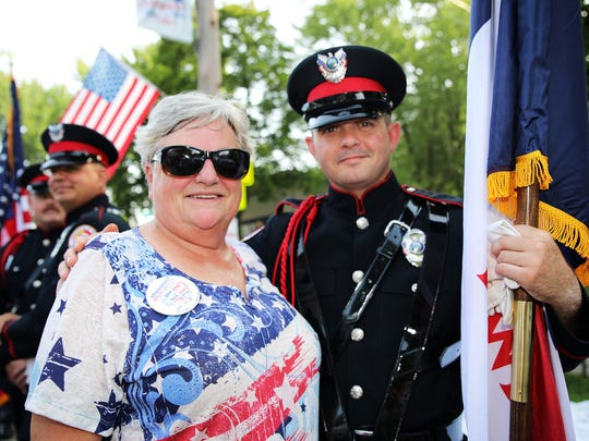 "Former Urbandale City Council Member Mary Polson and Zac McDowell of the Urbandale Police Dept. wait for the start of the Urbandale Fourth of July parade along 70th street on Wednesday, July 4th in Urbandale.  The parade theme for 2018 is ""Honoring Our First Responders""."