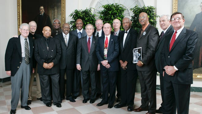 """President George W. Bush poses with members of the 1966 Texas Western Championship Basketball Team, Wednesday evening, Feb. 22, 2006, prior to screening the movie """"Glory Road"""" at the White House  The movie chronicles the Texas Western team's first time all-black lineup in the 1966 NCAA playoffs and upsetting the favored University of Kentucky team to win the national title."""
