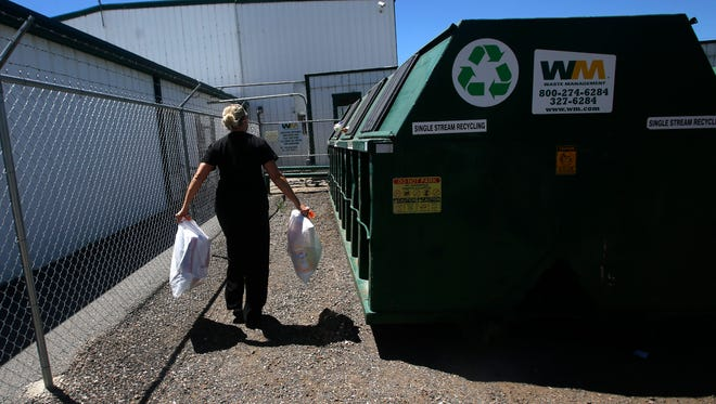 Jennifer Malone carries her recyclables to to a bin Monday at the Waste Management Recycling Center in Farmington,