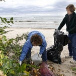 Jeanne Turner, of Rochester, left, and her daughter, Melissa Mandzak, of Geneseo, pick broken glass from a walking path during the annual International Coastal Clean Up project at Durand-Eastman beach in September 2010. (Democrat and Chronicle staff photo by Kris J. Murante, (9/25/2010)