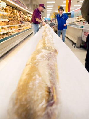 Bud Sabel of St. Peter Lions and Charlotte Nelson lay out sections of a sub sandwich at Pick 'n Save in this file photo.