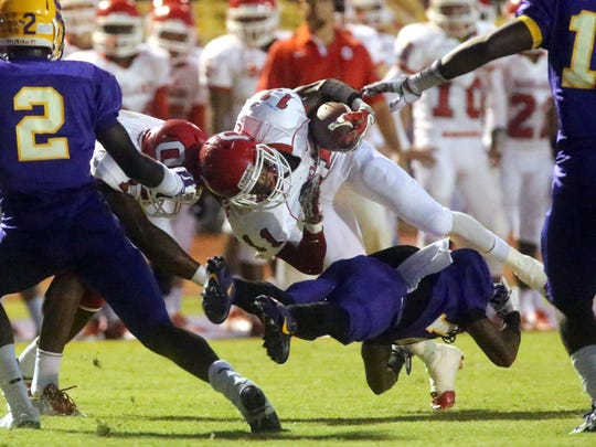 Oakland's Josh Cunningham runs the ball as Smyrna's D. J. Williams trips Cunningham up in the first half of the game  at Smyrna, on Friday, September 19, 2014.