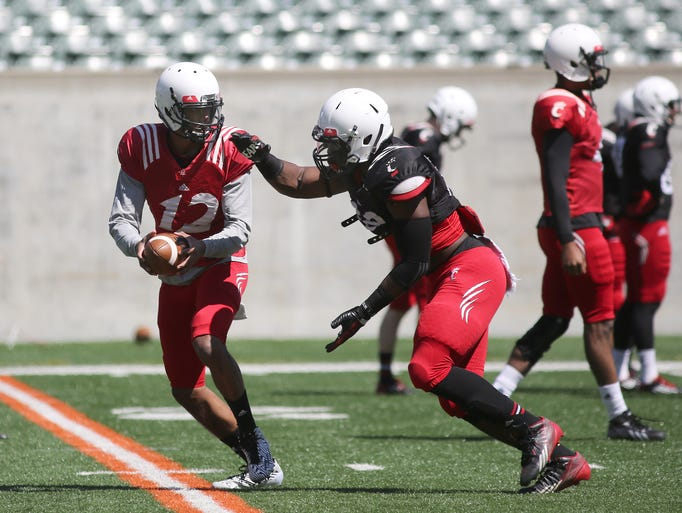 Jarred Evans (12) hands off the ball during drills before a University of Cincinnati intrasquad scrimmage at Paul Brown Stadium on Sunday.