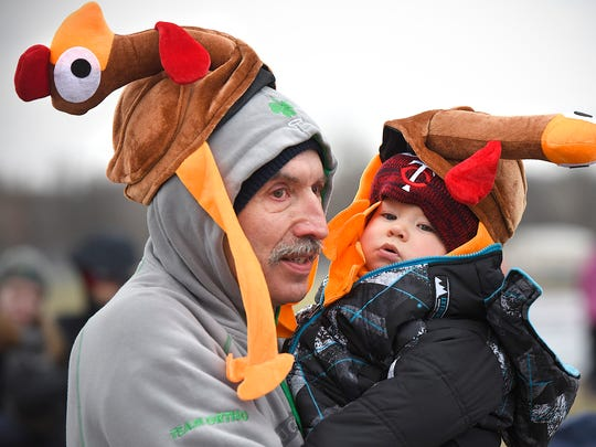 Mike Murphy and his grandson Carter Ellingboe, 10-months, cuddle to stay warm before the start of the CentraCare Health Wishbone Run Thursday, Nov. 26 at Whitney Park. About 3,000 runners and walkers took part in the annual 1K and 5K runs.