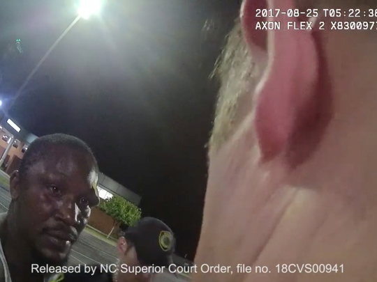 Johnnie Rush is seen in a screengrab taken from the body-worn camera of Christopher Hickman on August 25, 2017, at 1:22 a.m. The recording is taken in the parking lot of Mission Hospital following Mr. Rush's release from the hospital. The video shows Christopher Hickman, Officer Verino Ruggiero and Mr. Rush talking about the earlier incident in the Mission Parking lot, and then the drive to the Buncombe County Detention Facility.