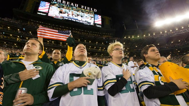 Scott Sheffield (second from left) and his sons, Connor and Spencer, stand for the national anthem before the Green Bay Packers game against the Chicago Bears  on Thursday at Lambeau Field in Green Bay. The family from St. George, Utah, said they weren't going to lock arms because that gesture seemed more like an anti-President Trump protest. To demonstrate unity, Green Bay Packers quarterback Aaron Rodgers asked fans to join players, locking arms in the stands during the national anthem.