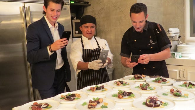"""""""I'm from Spain. Of course, I'm going to serve octopus,"""" says Jose Fernandez, far right, the new executive chef at Four Seasons Hotel Westlake Village. He shares a laugh, and a photo session, with cook Gadiel Carrillo, center, and Harley Potter, left, while preparing a private, nine-course dinner at the hotel this month."""