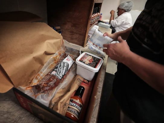 Pat Donohue preps a box of barbecue for sale at the