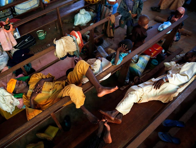Muslim men sleep inside the St. Pierre church where they and hundreds of other Muslims seek refuge outside the capital of Central African Republic on Jan. 23.  Clashes erupted between Anti-Balaka Christians and Seleka militias on the day of the inauguration of Central African Republic's interim President Catherine Samba-Panza, as thousands tried to flee the looting of their neighborhoods.