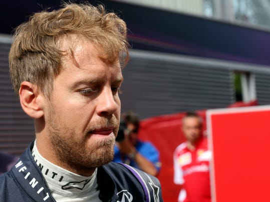 Red Bull driver Sebastian Vettel of Germany walks in the paddock prior to the start of the third practice session ahead of the Spain Formula One Grand Prix at the Barcelona Catalunya racetrack in Montmelo, near Barcelona, Spain, Saturday, May 10, 2014. Vettel's car rolled to a halt during Friday's first practice session, and it failed him again early in the third period of qualifying.(AP Photo/Luca Bruno)