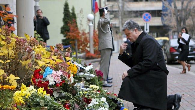 Ukrainian president Petro Poroshenko kneels to mourn for the victims killed in the Friday's attacks in Paris, France, in front of the French Embassy in Kiev, Ukraine, Saturday, Nov. 14, 2015.(AP Photo/Sergei Chuzavkov)
