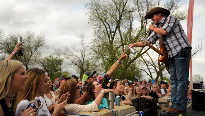 Singer Kyle Park takes a beer handed to him by a fan while performing in the 2017 Outlaws and Legends Music Fest on Saturday, April 1, 2017, at the Back Porch of Texas.